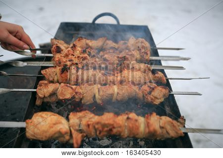 The pork shish kebab on skewers prepares on a brazier in the winter on the backyard.