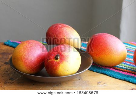 Whole ripe mangos on a table with colorful place mat and with selective focus on mangos in foreground