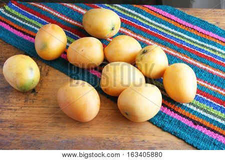 Ten whole ripe yellow mangos with a colorful place mat on a wooden table.