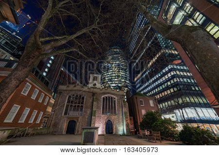 An old church in central London with the modern skyscrapers of the City of London rising around it.