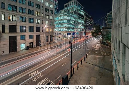 London, UK. 28th December 2016. Traffic passes along Lower Thames Street in central London on a cold winter's evening against the backdrop of office buildings and shops.