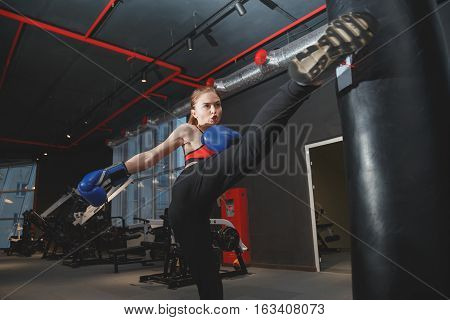 Kickboxing young woman punching kicking the bag
