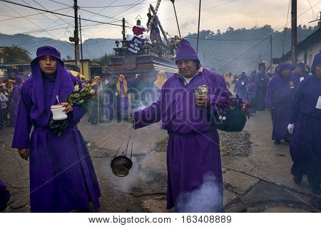 Antigua Guatemala - April 16 2014: Man wearing purple robesin a procession during the Easter celebrations in the Holy Week in Antigua Guatemala.