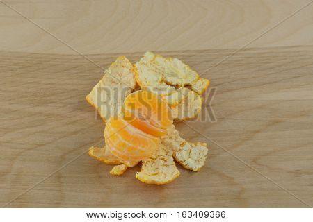 Part of Mandarin clementine orange sitting in peel on wooden table
