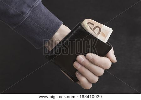man holding a purse with money in hand; hipster