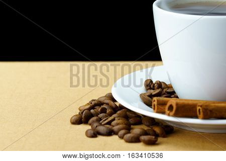 Mug of black coffee with cinnamon and beans