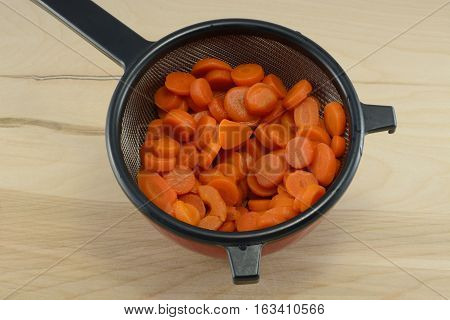 Rinsed sliced canned carrots draining in strainer in bowl to remove salt on wooden table