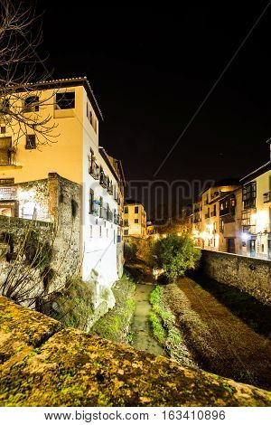 Urban scene of a river crossing the old part of the city of Granada Spain taken at night