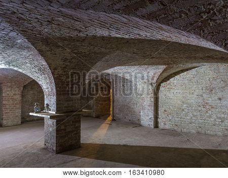 Cellar room made of brick with curved ceiling and an entrance with a shaft of light beaming in.