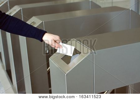 Woman's hand puts white plastic card to reader access security control system closeup