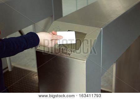 Woman's hand puts white plastic card to reader security access control system closeup