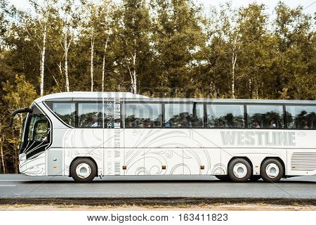 NEAR MOSCOW RUSSIA - AUGUST 11 2012: touring bus with passengers goes along a forest road