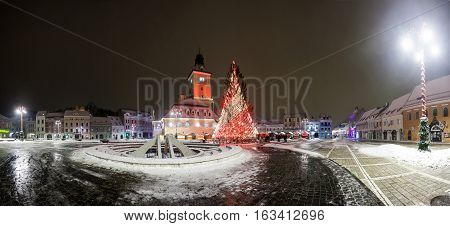 BRASOV ROMANIA - 15 DECEMBER 2016: Brasov Council House panoramic night view with Christmas Tree decorated and traditional winter market in the old town center Romania