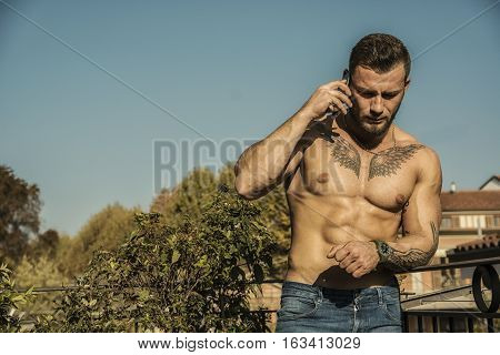 Handsome shirtless muscular young man outdoor on a balcony or terrace, talking on cell phone, wearing only jeans, looking away