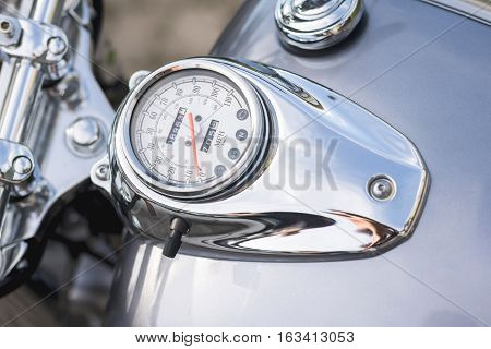 Motorcycle handlebar controls including speedometer. Vintage chrome vehicle parts.