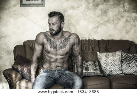 Handsome shirtless muscular young man at home laying on couch