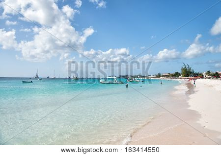 Bridgetown Barbados - December 12 2015: sandy beach at sea or ocean coast with people and transportation of boats and ships sunny outdoor on sky background