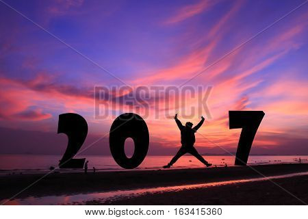 young man jumping on the sea and 2017 years while celebrating new year