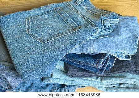 Many colored jeans on sandy brown background closeup