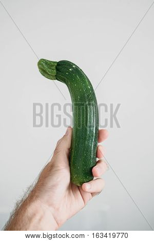 Organic zuchinni vegetable in human hand against light gray background