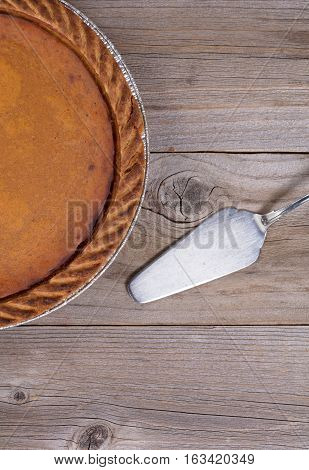 Overhead view of Pumpkin pie and spatula server on rustic table in vertical format