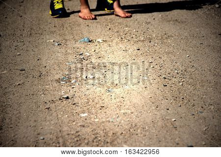 A pair of feet standing on a dirt road. Bare feet of young boy.