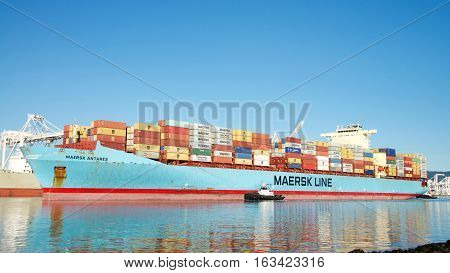 Oakland CA - December 28 2016: Cargo Ship MAERSK ANTARES with multiple tugboat assisting to maneuver the vessel into the Port of Oakland.