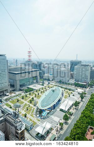 Travel concept - Panoramic modern city bird eye view on Nagoya TV Tower landmark of Nagoya. Oasis21 Aichi art center and holly tree plaza under modern city with blue and sunny morning sky in Japan
