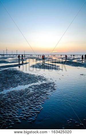 Asia culture - Beautiful landscape of sea level reflect fantasy dramatic sunset sky and people's silhouette in Gaomei wetlands the famous travel attractions in Taichung Taiwan.