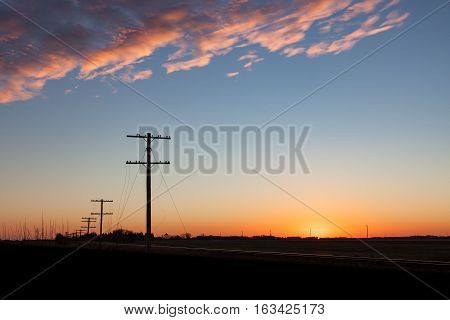 Silhouetted telephone lines at sunrise outside Winnipeg Manitoba.