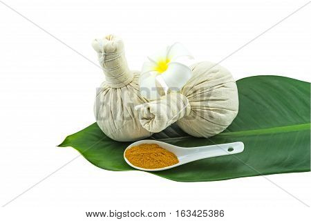 Spa herbal compressing ball white frangipani flowers (Plumeria spp flower Apocynaceae flower Pagoda tree flower Temple tree flower) turmeric powder in white spoon in green leaf isolate on white background.Saved with clipping path
