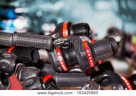 Close view of many bicycle gears shifters and handlebars in on place