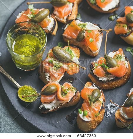 Homemade salmon crostini with cream-cheese, watercress, capers and pesto suace in round black slate stone plate over grey background, selective focus, square crop