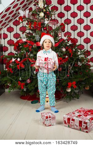Amazed boy holding Christmas gift in front of tree