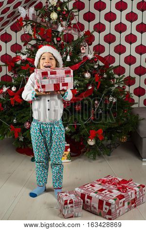 Amazed cheerful kid dressed in festive clothes holding Christmas gifts