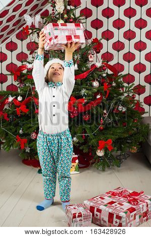 Cheerful boy raising Christmas gift above the head in front of tree