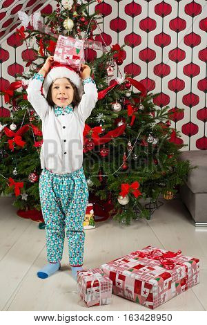 Boy holding Christmas gift above the head