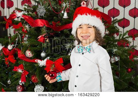 Cheerful little boy with Santa hat holding bauble