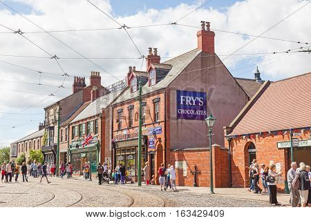 BEAMISH UK - JULY 27 2012: Tourists shops and tramlines in the high street of the Edwardian town that forms part of Beamish Museum in County Durham England. Beamish is a world-famous open-air museum that tells the story of life in North-East England.