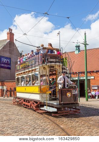 BEAMISH UK - JULY 27 2012: 'Newcastle 114', a tram built in 1901, trundles down the high street of the Edwardian town that forms part of Beamish Museum in County Durham, England. Beamish is a world-famous open-air museum.