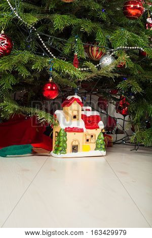Ceramic colorful house under Christmas tree in living