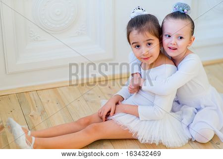 Two Young Ballet Dancers Hug