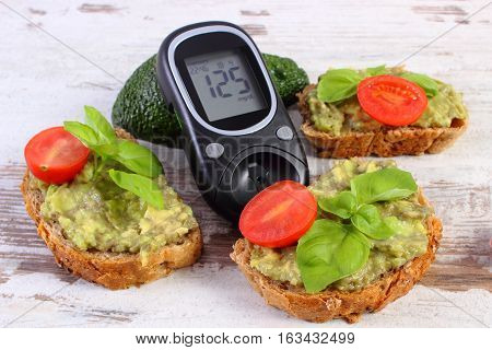 Glucose meter with result of measurement sugar level and freshly sandwiches with paste of avocado concept of diabetes healthy food nutrition and omega fatty acids