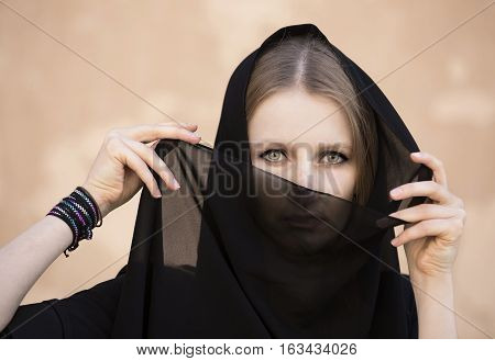 young woman in traditional dress (abaya) in Jabrin Castle in Oman