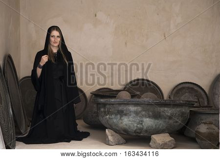 young woman in an abaya, traditional emirati dress, in a kitchen surrounded by old cooking utensils