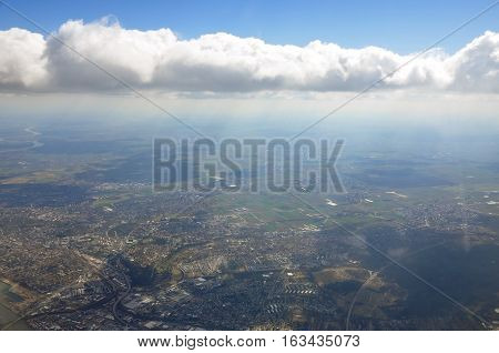 Sky scenery. Aerial view over the cumulus clouds with sun rays. Flying over the city.