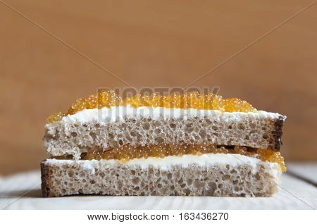 Multilayer sandwich of bread cream cheese and pike caviar close-up on light wood surface. Side view empty place.