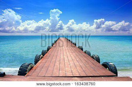 Jetty at the beach with cloudy blue sky