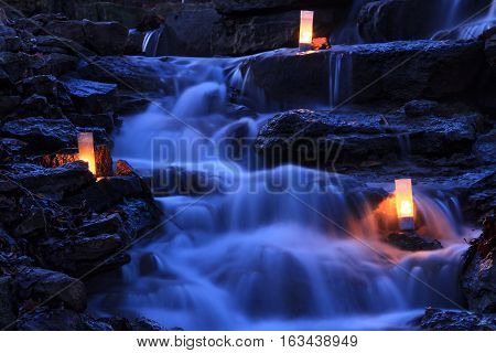 Cascading waterfall garden at twilight with candles glowing on the rocks.