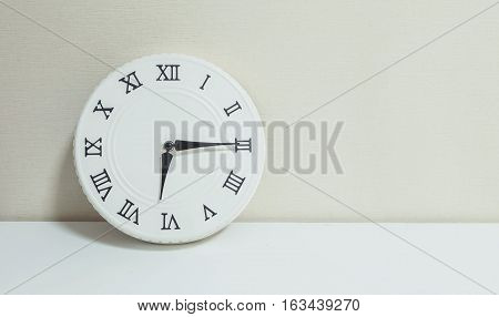 Closeup white clock for decorate show a quarter past six or 6:15 a.m. on white wood desk and cream wallpaper textured background with copy space